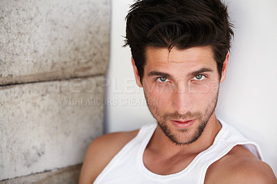 Buy stock photo Portrait of a good-looking young man staring up at you leaning against a wall alongside bricks - Copyspace