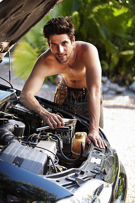 Buy stock photo Portrait of an attractive man smiling while repairing his car engine with a spanner in his hand
