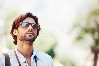 Buy stock photo Shot of a handsome young man standing outdoors