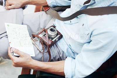 Buy stock photo Closeup cropped image of a young male resting a map and camera on his lap
