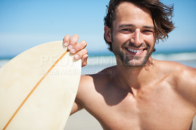 Buy stock photo An attractive young man holding his surfboard on the beach