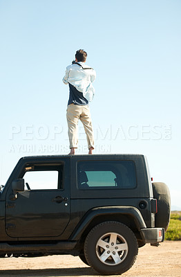Buy stock photo A young man getting up on the car for a better view