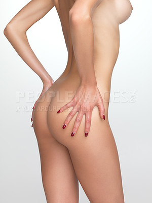 Buy stock photo Cropped rear view of a shapely woman's buttocks isolated on grey