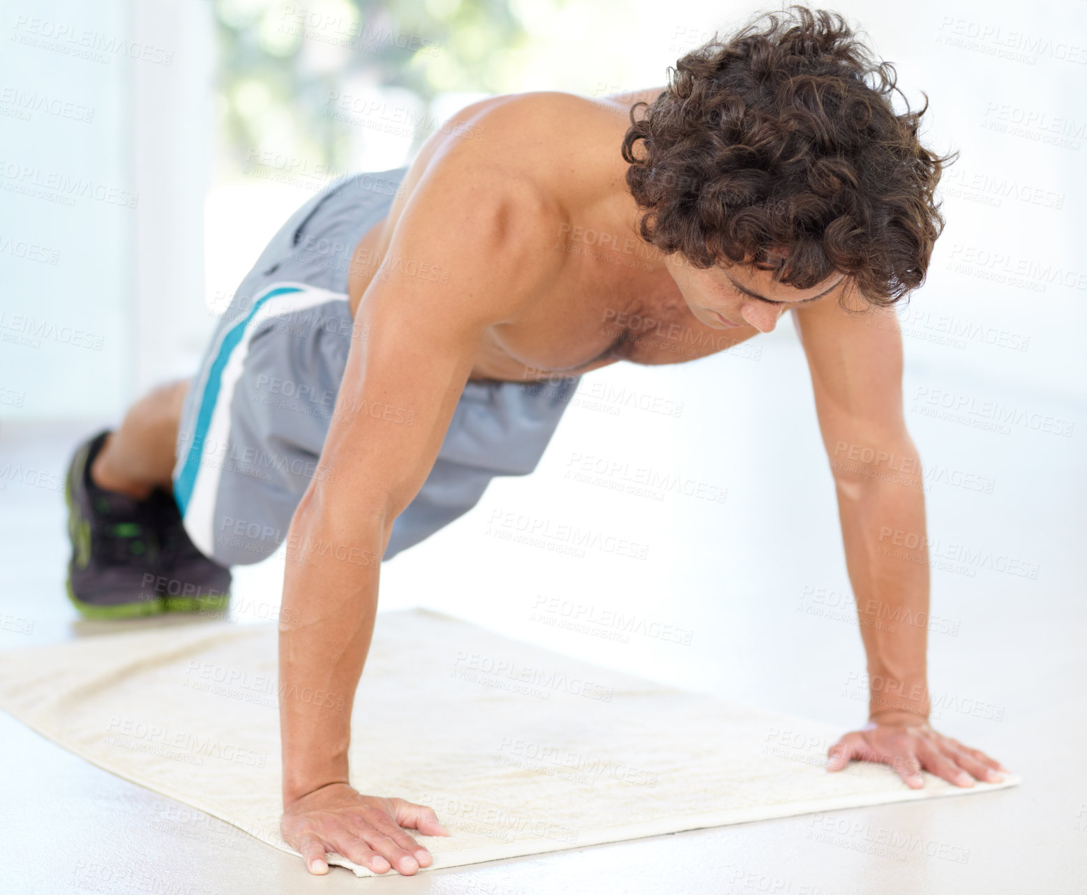 Buy stock photo A sexy young man doing pushups on the floor