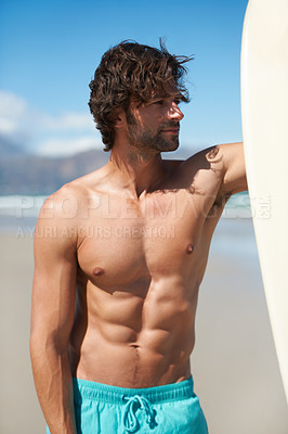 Buy stock photo A young man standing next to his surfboard looking around