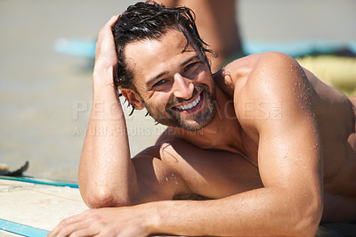 Buy stock photo A young man relaxing and smiling while lying on his surfboard on the sand