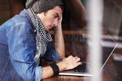 Buy stock photo Shot of a young man sitting at a laptop
