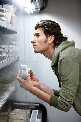Buy stock photo A young man comparing the prices of some items