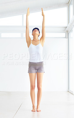 Buy stock photo Young woman stretching towards the ceiling in fitness gear