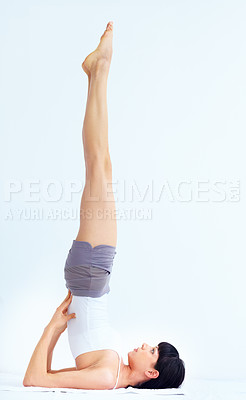 Buy stock photo Young fit woman in a yoga position while isolated on white