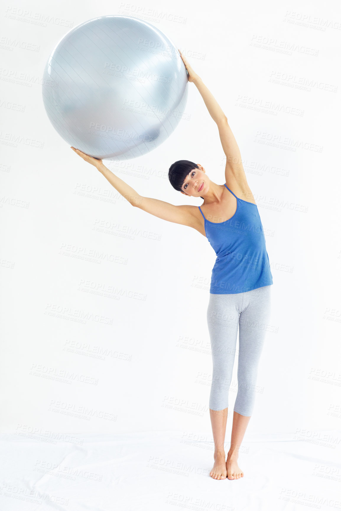 Buy stock photo Fit young woman exercising while holding an exercise ball