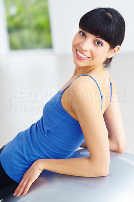 Buy stock photo Smiling young woman leaning against an exercise ball