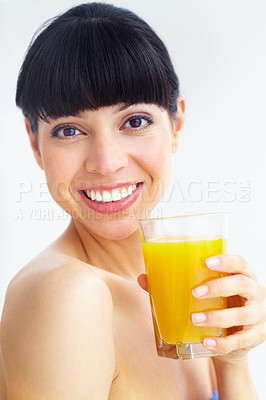 Buy stock photo Portrait of a smiling young woman enjoying a glass of orange juice