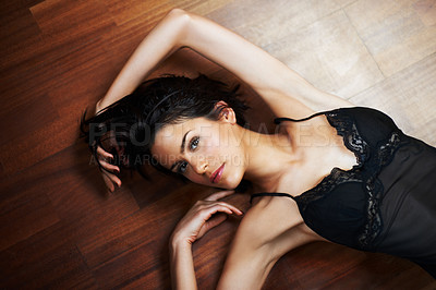 Buy stock photo Sensual woman wearing a black nightdress lying on a wooden floor gazing up at you