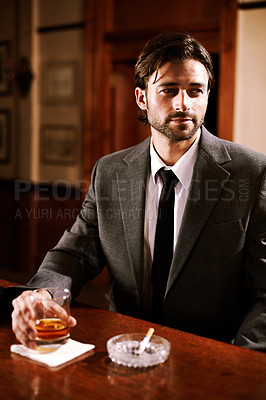 Buy stock photo A well-dressed young man sitting at a bar with a drink