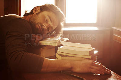 A handsome young man sleeping on a pile of books