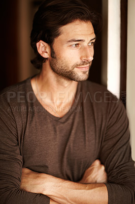 Buy stock photo A handsome young man gazing out of a window with his arms folded