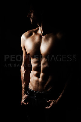 Buy stock photo Low-key image of a muscular young man on a black background