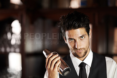 Buy stock photo Portrait of a handsome young bartender mixing a cocktail for a customer