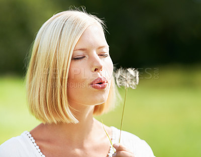 Buy stock photo Cute young woman blowing at a dandelion