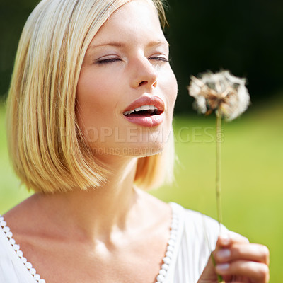 Buy stock photo Cute young woman preparing to blow at a dandelion