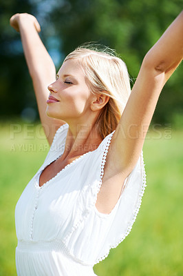 Buy stock photo Lovely young woman standing outdoors enjoying the country air with her arms outstretched