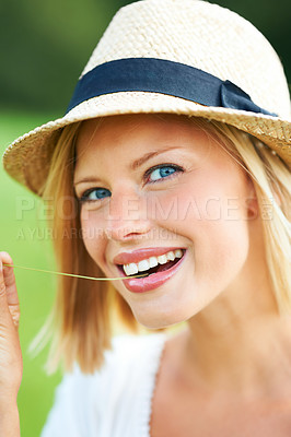Buy stock photo Lovely young woman smiling while wearing a hat and chewing a wheat stalk