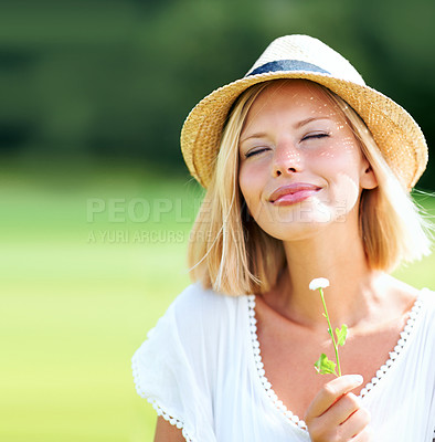 Buy stock photo Pretty young woman wearing a hat and smiling while holding a tiny flower