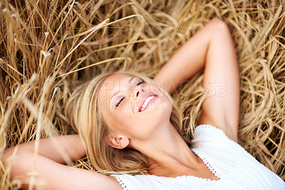 Buy stock photo Smiling young woman lying in a field of wheat