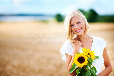 Buy stock photo Gorgeous young woman smiling in a wheat field while holding some sunflowers