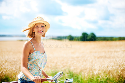 Buy stock photo Cute young woman riding a bicycle in the countryside