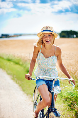 Buy stock photo Happy young woman riding a bicycle in the countryside