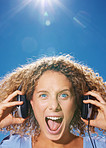 Closeup of excited young girl listening to music and screaming