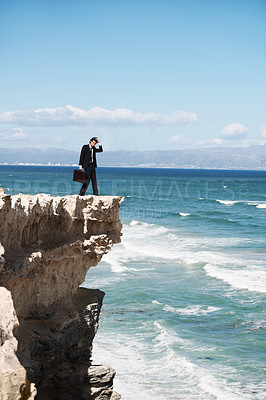 Buy stock photo Confused businessman standing on the edge of a cliff overlooking the ocean