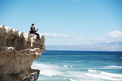 Buy stock photo Young businessman sitting on the edge of a cliff overlooking the ocean while reading a book