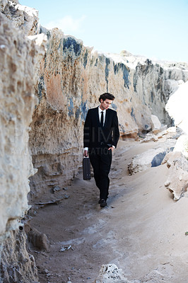 Buy stock photo Handsome businessman strolling along the sand next to a rock formation, carrying a briefcase