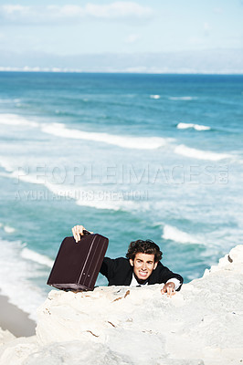 Buy stock photo Businessman climbing up the side of a cliff overlooking the ocean  with his his briedcase