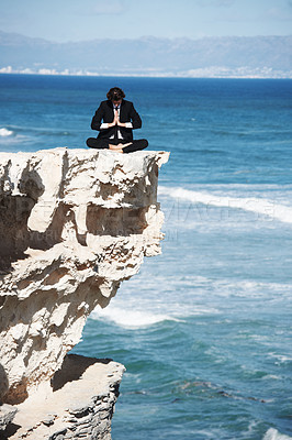 Buy stock photo Businessman meditating on top of a cliff above the ocean