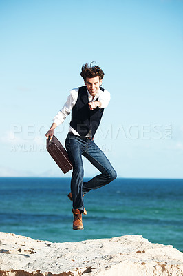 Buy stock photo Handsome young man holding a briefcase jumping in the air with the ocean in the background