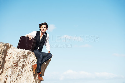 Buy stock photo Young businessman sitting with his legs dangling over the side of a cliff next to copyspace