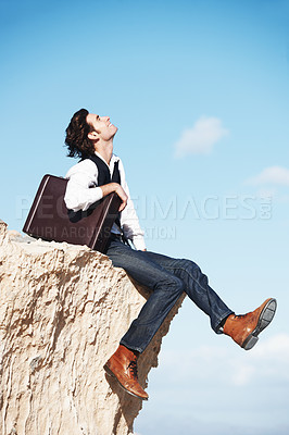 Buy stock photo Smiling young man sitting with his briefcase on the edge of a cliff overlooking the ocean