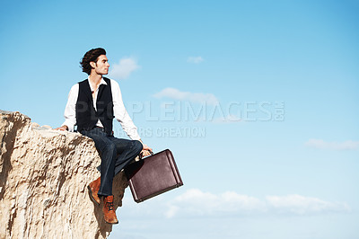 Buy stock photo Handsome businessman sitting with his legs dangling over the side of a cliff next to copyspace
