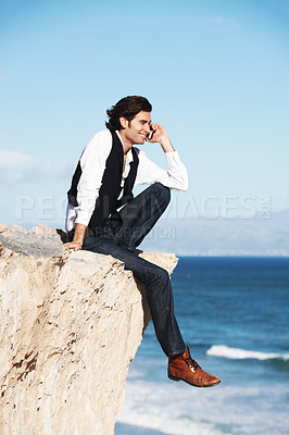 Buy stock photo Smiling young man chatting on his phone while sitting on a cliff overlooking the ocean