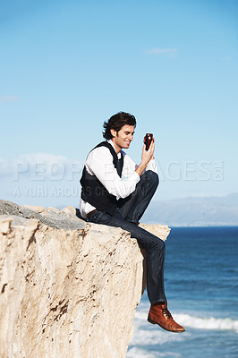 Buy stock photo Smiling young man texting on his phone while sitting on a cliff overlooking the ocean