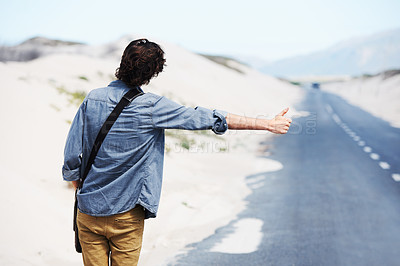 Buy stock photo Rear-view of a trendy young man hitchhiking on the side of the road