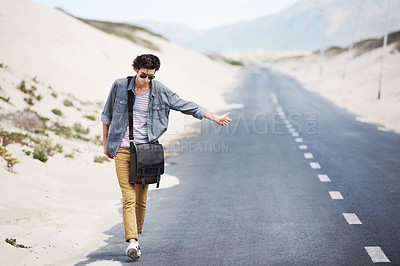 Buy stock photo Handsome young man hitchhiking while walking down the side of the road
