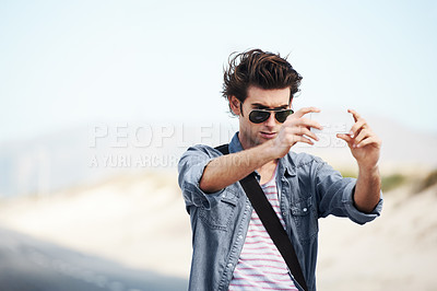 Buy stock photo Trendy young man standing on the road and taking a picture on his phone