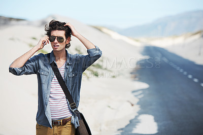 Buy stock photo Trendy young man on the side of the road speaking on his cellphone while looking worried