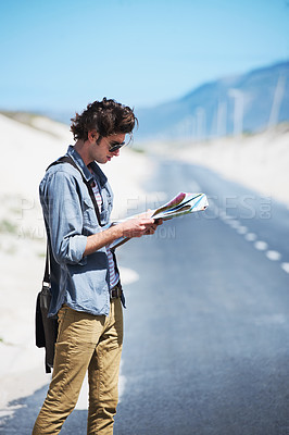 Buy stock photo Young man standing on the side of the road reading a map