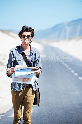 Buy stock photo Lost young man standing on the side of the road holding a map and looking confused